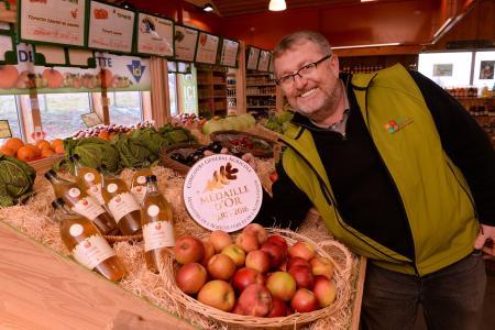 Didier Vecten avec son jus de pomme médaillé dans son magasin Esprit Terroirs